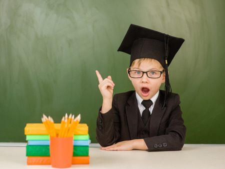 graduated: Surprised boy in graduation cap points on empty green chalkboard.