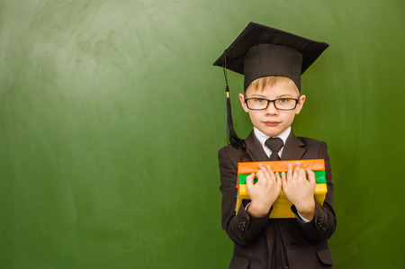 Serious boy in graduation cap with books standing near green chalkboard.