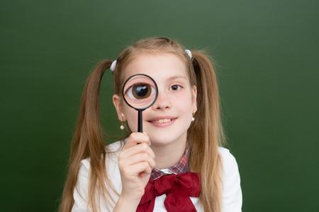 Happy girl holding on eye magnifying glass loupe. Stock Photo