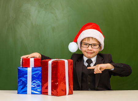 Happy boy in red christmas hat near empty green chalkboard points on on the gift boxes. Stock Photo