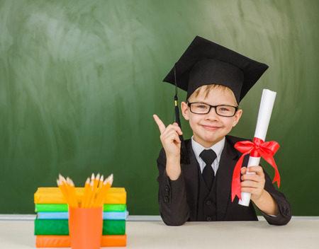 Happy boy with diploma in graduation hat points on empty green chalkboard. Stock Photo