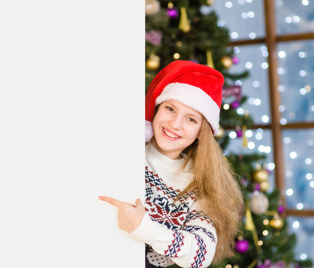 Happy teen girl in red christmas hat peeking and pointing at empty board. Stock Photo