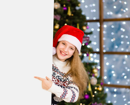 Happy girl in christmas hat peeking and pointing at empty board.