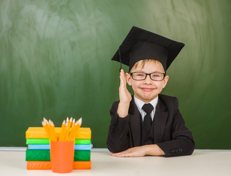 Happy boy in graduation hat and in a suit raising hand knowing the answer to the question. Stock Photo