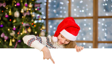 Happy teen girl in christmas hat peeking and pointing down at empty board. Space for text. Stock Photo