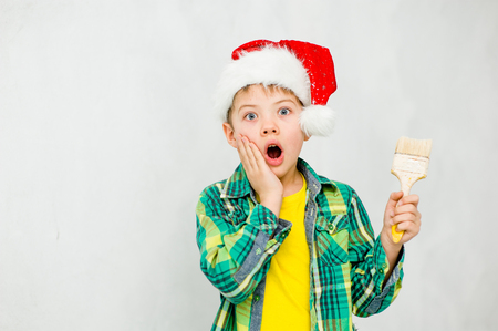 Surprised boy in a red christmas hat with paintbrush in hand. Stock Photo
