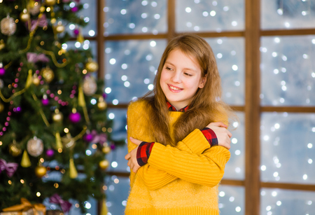 Portrait of blonde teen girl in red christmas hat on the background of Christmas tree. Stock Photo