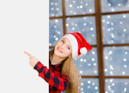 forefinger: Happy teen girl in red christmas hat peeking above white banner and pointing away.