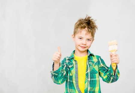 Happy boy with paintbrush showing thumbs up. Stock Photo