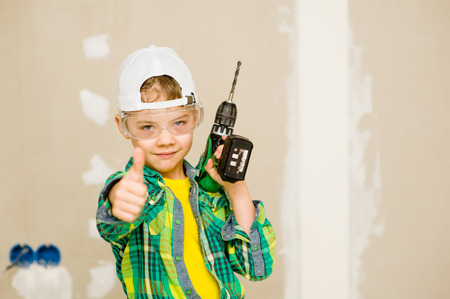 Happy boy with drill showing thumbs up. Stock Photo