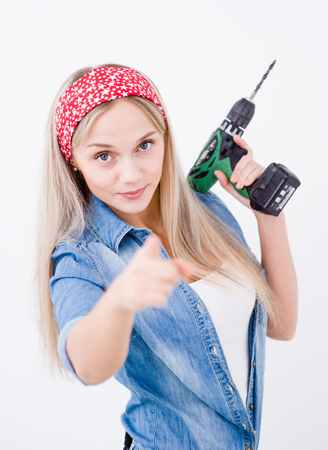 choise: Smiling woman with drill pointing her finger to you.