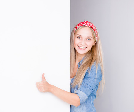 thumbsup: Young housewife looks above white banner