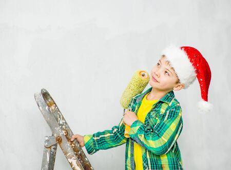 Pensive boy in a red christmas hat holding roller for painting.