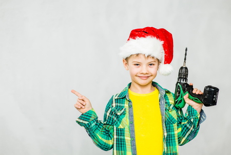 forefinger: Boy in a red christmas hat with a drill points to empty space.