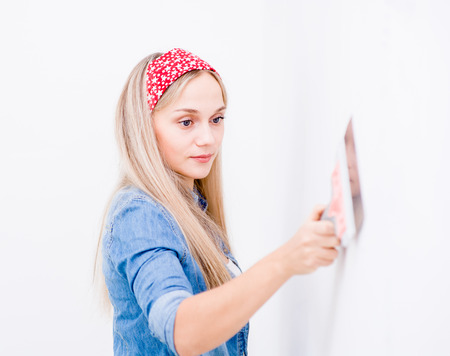 Happy woman repairs wall with spackling paste.