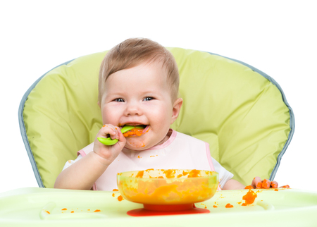 smeared baby: Happy baby sitting in high-chair with spoon and plate. Stock Photo