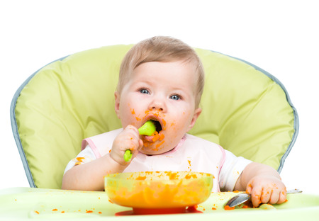 eat smeared: Baby girl eats with spoon.