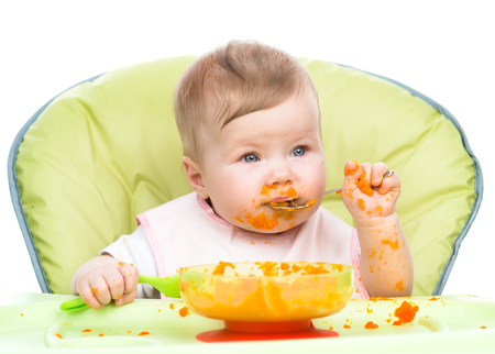 Little baby are eating with spoon.