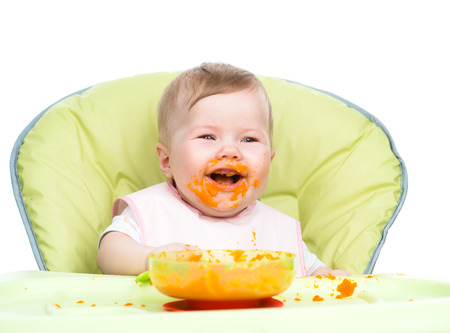 Happy baby with spoon sits at highchair and eats carrot puree.