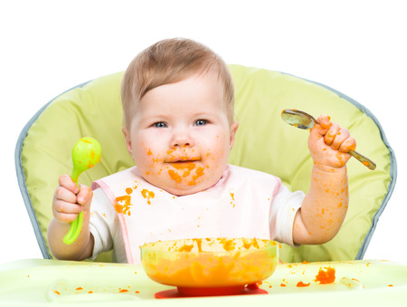 Happy baby sitting in high-chair with spoon and plate. Stock Photo