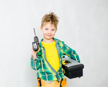 Young boy with tool belt holding drill and toolbox. Stock Photo