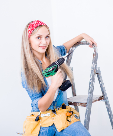renew.: Portrait of a happy woman on a ladder with drill. Stock Photo