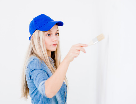 renew.: Young woman painting the wall with paintbrush.