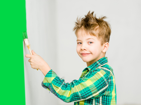 Young boy painting the wall with paintbrush.