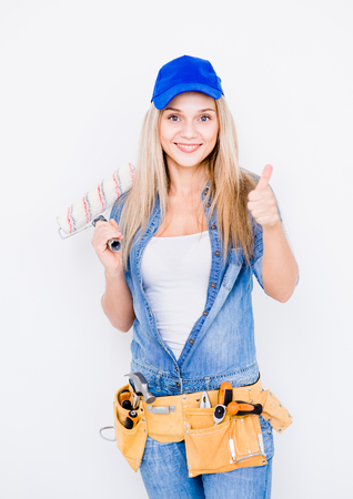 Beautiful young woman with paint roller and tool belt showing thumbs up. Stock Photo