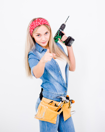 towards: Beautiful young woman contractor with toolbelt and drill on white pointing her finger to you.