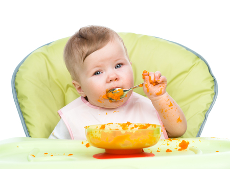 smeared baby: Little baby are eating with spoon.
