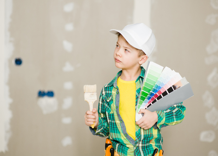 work from home: Boy with color samples and paintbrush chooses the color of the walls of his room.