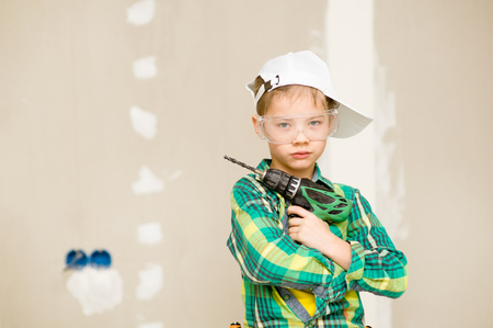 work from home: Boy with a drill in hands looking at camera. Stock Photo