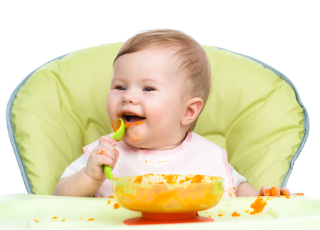 smeared baby: Happy baby sitting in high-chair with spoon and plate. isolated on white background.
