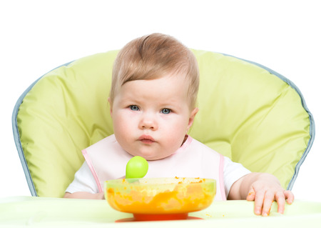 smeared baby: Baby sitting in high-chair with spoon and plate. isolated on white background.
