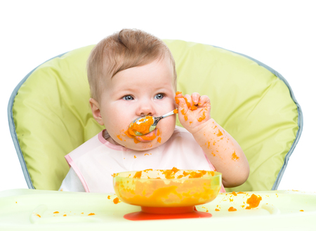 smeared baby: Little baby are eating with spoon. isolated on white background.