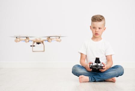 Boy is operating the drone by remote control. Foto de archivo