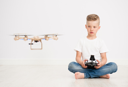 Boy is operating the drone by remote control. Banco de Imagens