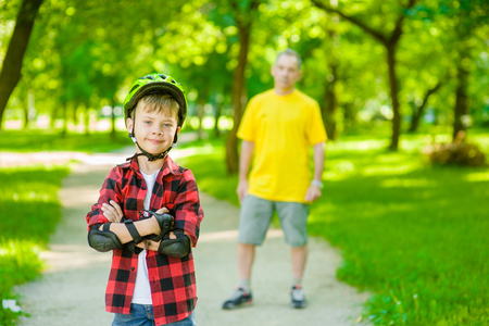 skate park: Portrait of a boy with arms crossed in a protective helmet and protective pads for roller skating on the background of his father.