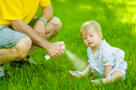 Father spraying insect repellents on skin his daughter. 스톡 콘텐츠