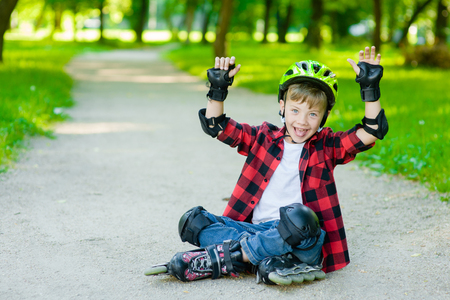 Happy boy in a protective helmet and protective pads for roller skating. Space for text.