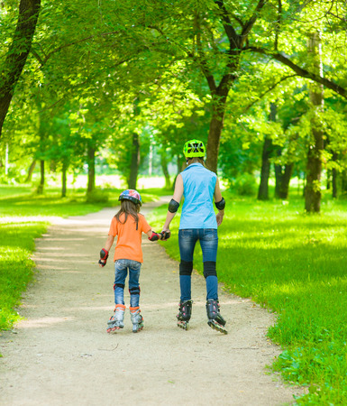 Mom and daughter together rollerblading. Back view.