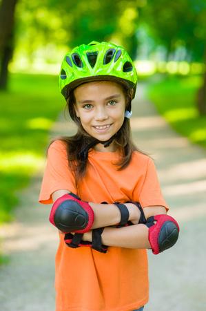 Retrato de una muchacha con los brazos cruzados en un casco protector y cojines protectores para el patinaje de ruedas.
