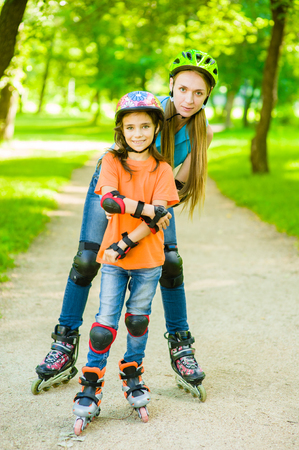 teaches: Mother teaches her daughter to ride roller skates.