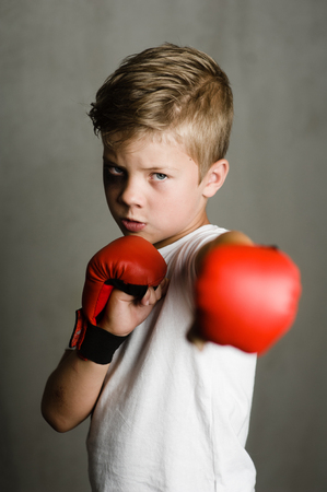 Beaten young boy punching with red boxing gloves.