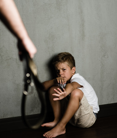 Domestic violence: father hand with belt and frightened beaten son. Standard-Bild