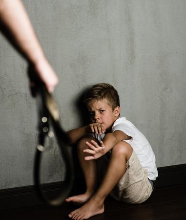 Huishoudelijke geweld: vader hand met riem en bang beaten zoon. Stockfoto