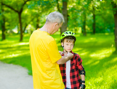 Father fastens a protective helmet to his son. Stock Photo