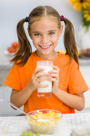 Happy little girl with milk mustache holding glass of milk. Stock Photo