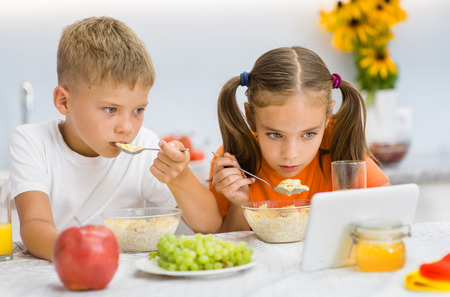 Brother and sister eat breakfast while watching a movie on a tablet.